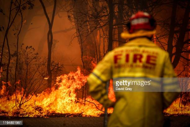 Fire and Rescue personnel watches a bushfire as it burns near homes on the outskirts of the town of Bilpin on December 19 2019 in Sydney Australia...