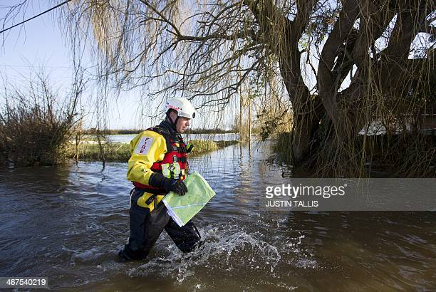 A Fire and rescue services officer wades through floodwaters during flood relief operations in Moorland some 19 Kms Northeast of Taunton on February...