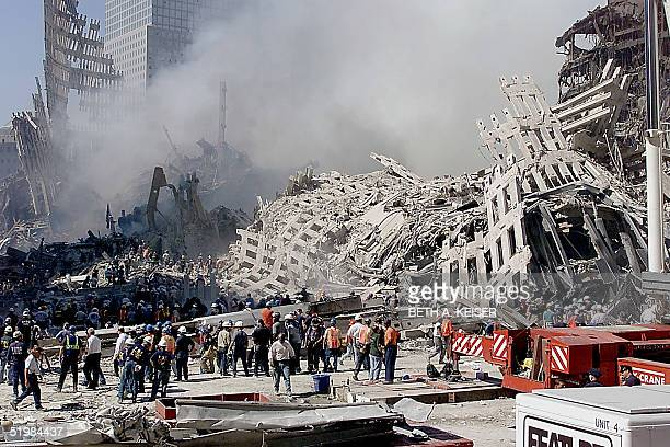 Fire and rescue workers search through the rubble of the World Trade Center 13 September 2001 in New York Rescue and cleanup continues after the twin...