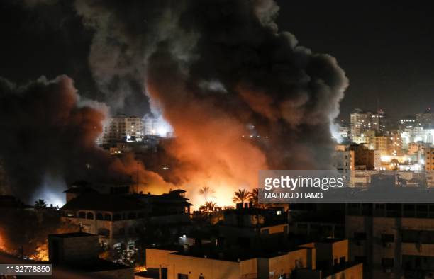 Fire and smoke billow above buildings in Gaza City during reported Israeli strikes on March 25 2019 Israel's military launched strikes on Hamas...