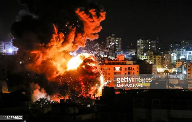 TOPSHOT Fire and smoke billow above buildings in Gaza City during reported Israeli strikes on March 25 2019 Israel's military launched strikes on...