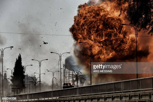 Fire and smoke billow following a car bomb explosion as Iraqi forces clash with Islamic State group fighters in Mosul on March 5 during an offensive...