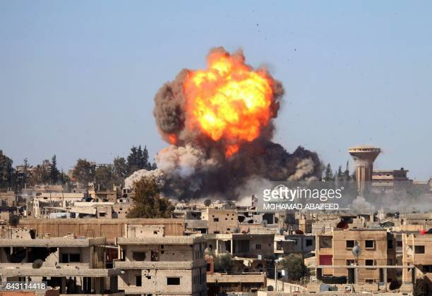 TOPSHOT Fire and smoke billow following a reported car bomb explosion at a Syrian progovernment position during clashes between rebel fighters and...