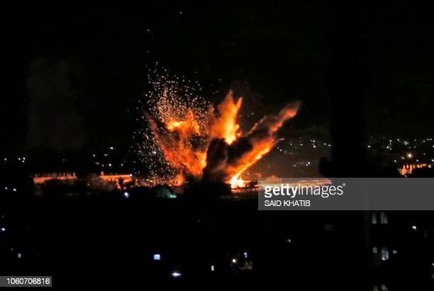 TOPSHOT Fire and smoke billow following Israeli air strikes targeting Rafah in the southern Gaza Strip near the border with Egypt on November 12 2018...