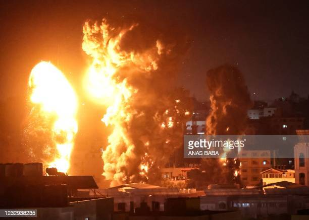 Fire and smoke rise above buildings in Gaza City as Israeli warplanes target the Palestinian enclave, early on May 17, 2021. - Israeli warplanes...