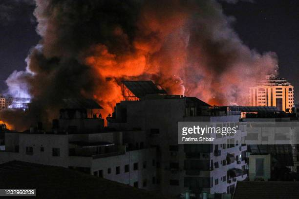 Fire and smoke rise above buildings in Gaza City as Israeli warplanes target a governmental building, early on May 18, 2021 in Gaza City, Gaza. More...