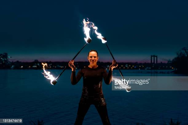 fire artist juggling with flaming torches - royal blue stock pictures, royalty-free photos & images