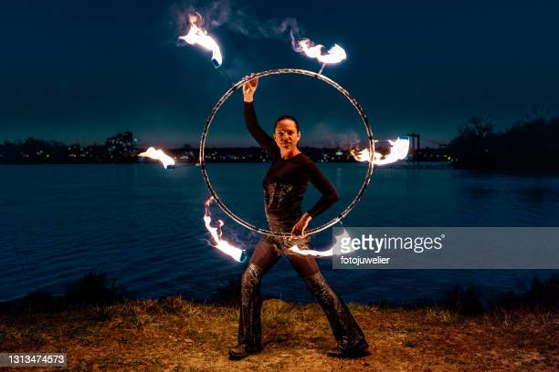 fire artist performing at night in front of river - royal blue stock pictures, royalty-free photos & images