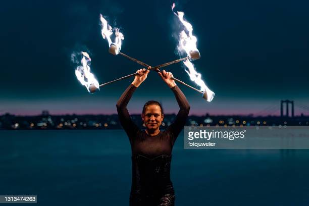 fire artist performing with flaming torches - royal blue stock pictures, royalty-free photos & images