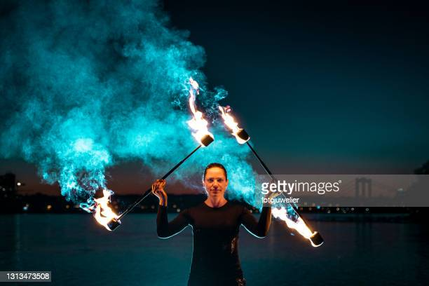 fire artist posing with flaming torches creating blue smoke - royal blue stock pictures, royalty-free photos & images