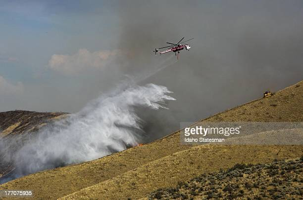A fire attack helicopter drops water along a draw at Hilltop Cafe northeast of Boise Idaho Tuesday August 20 2013 The blaze was reported to have...