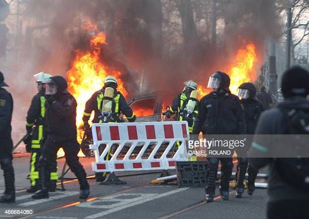 Fire brigade attempt to put out a police car burning on the opening day of the European Central Bank in Frankfurt am Main western Germany on March 18...