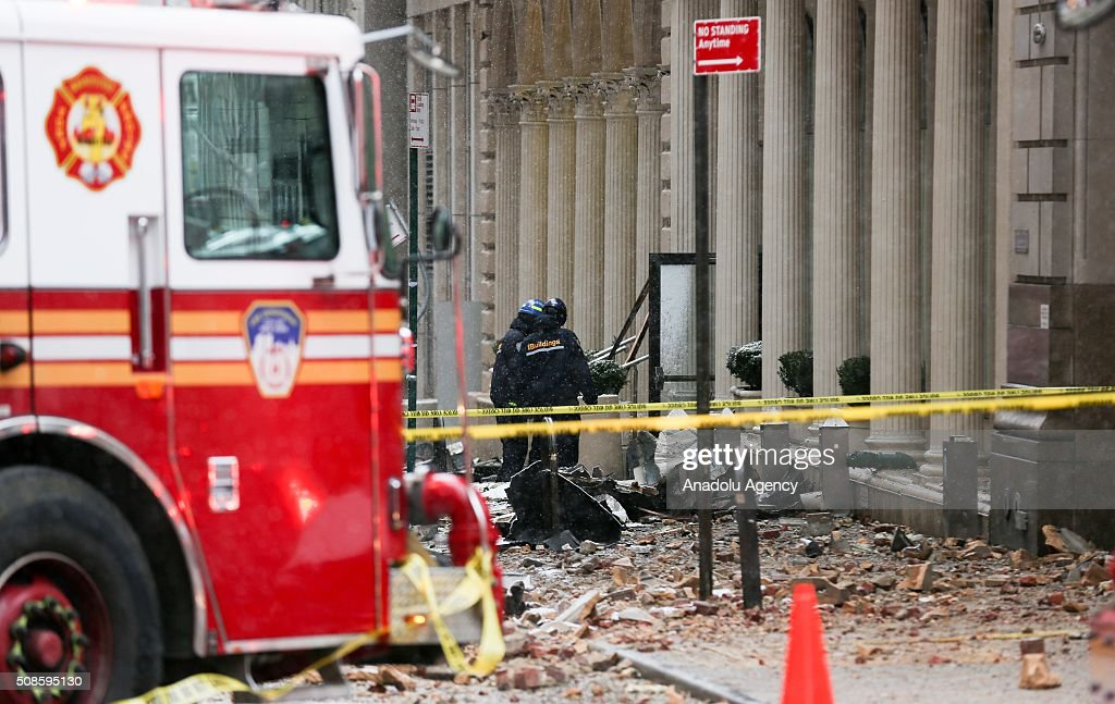 Fire brigade crew work at the scene of a collapsed crane on a roadway in lower Manhattan of New York, USA on February 5, 2016. A large construction crane has collapsed in lower Manhattan in New York City, killing one person and injuring at least two others.