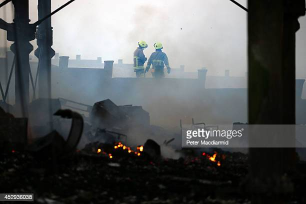 Fire Brigade officers work to damp down the remains of Eastbourne Pier after a fire broke out in the arcade on July 30 2014 in Eastbourne England The...