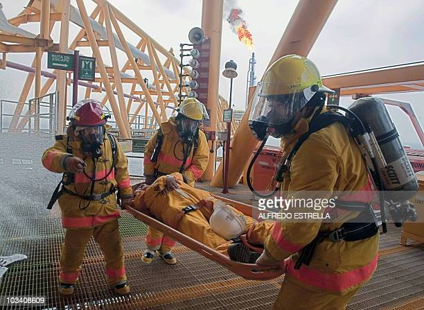 Fire brigade team personnel evacuate a 'casualty' during a fire drill aboard the Pemex KuS oil processing center part of the KuMaloob Zaap complex in...