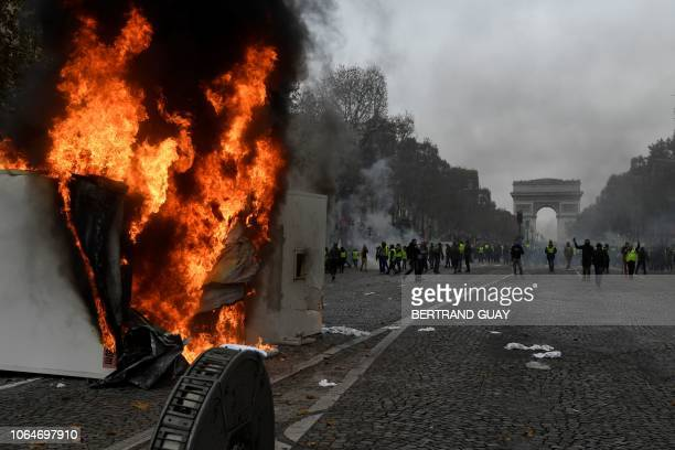 A fire burn as Yellow vests walk past the Arc of Triomphe on the Champs Elysees in Paris on November 24 2018 during a protest against rising oil...