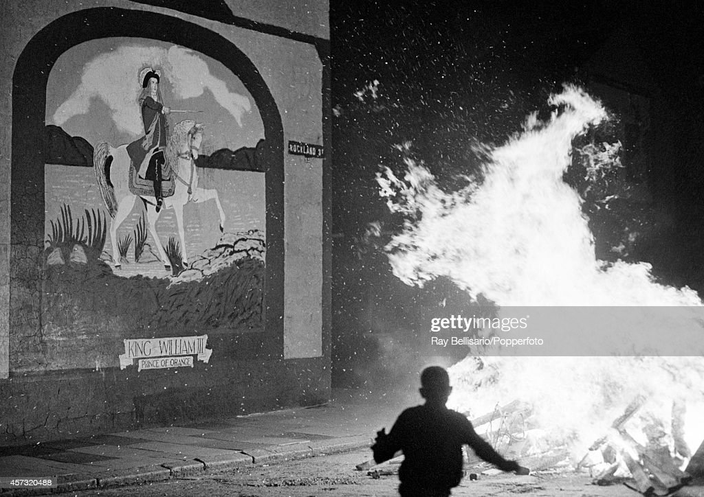 A fire burning next to a mural of King William of Orange after a day of marching by the Orange Order, a Protestant fraternal organiisation, in Belfast, Northern Ireland, circa July 1971.