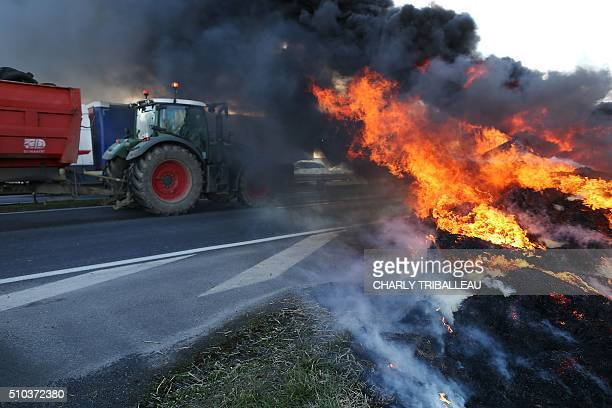 A fire burns as French farmers use tractors to block the ring road at the entrance of the city of Caen northwestern France on February 15 during a...