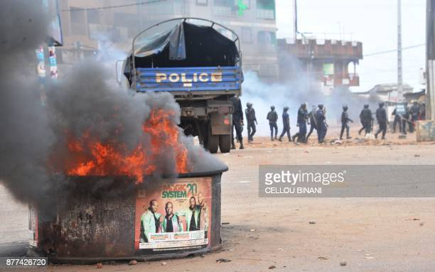 A fire burns as Guinean riot police officers patrol following clashes with protesters in a district of Conakry on November 21 2017 Thousands of...