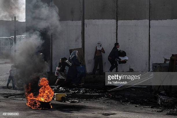 Fire burns as Palestinian protesters clash with Israeli border police on October 9, 2015 in Shuafat refugee camp in Jerusalem, Israel. As tension...