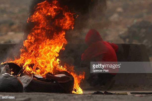 A fire burns as Palestinian youth clash with members of the Israeli military on January 16 2009 in Ramallah West Bank United Nations Secretary...