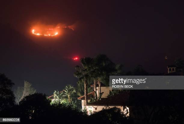 TOPSHOT Fire burns in the hills behind a home at the Thomas Fire December 16 2017 in Montecito California / AFP PHOTO / Robyn Beck