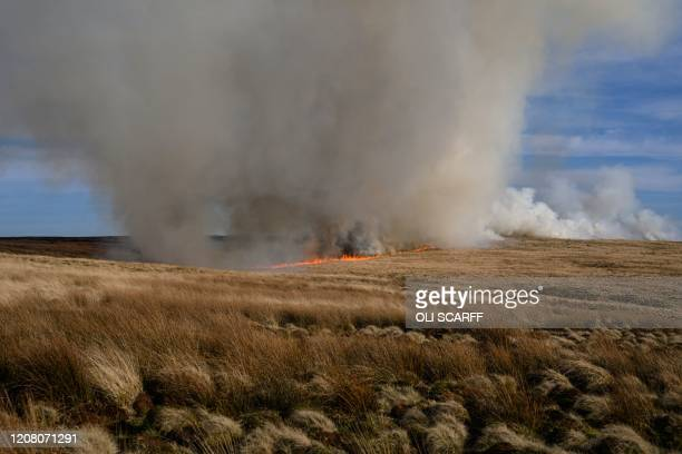 TOPSHOT A fire burns out of control on moorland above the village of Marsden in northern England on March 23 2020