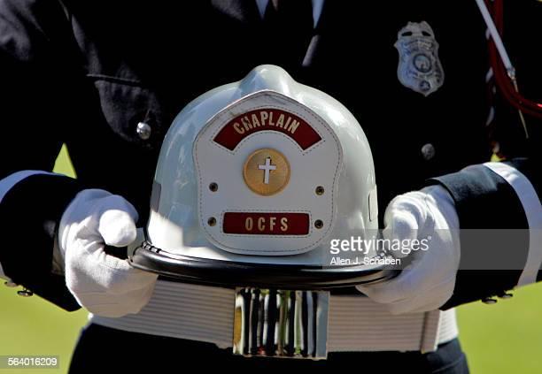 Fire Captain Steve King, Orange Co. Fire Authority, holds the Chaplain's helmet of Msgr. John Sammon, Orange County's oldest priest and a former fire...