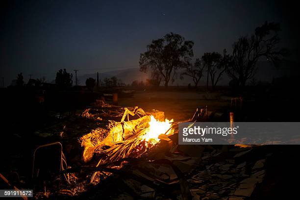 A fire continues to burn as the wreckage of a burned car sits along Highway 138 as the Blue Cut fire continues to ravage San Bernardino County Calif...