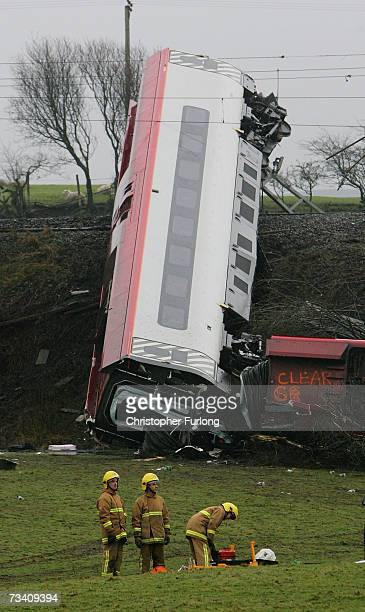 Fire crew attend the scene of a derailed carriage from a Virgin Express train as it lies wrecked on its side on February 24 2007 in Grayrigg Cumbria...