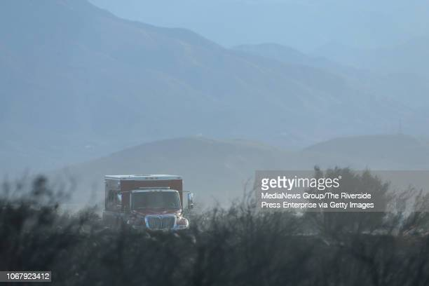 Fire crew sits parked watching for flare ups as high winds kick up dust on Wednesday, Nov. 14 after an overnight vegetation fire burned along...