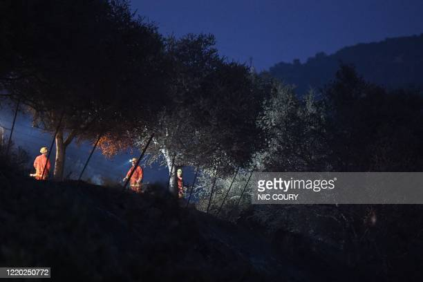 Fire crews clear brush near Highway 101 during Avila Fire in Pismo Beach, San Luis Obispo County, California, June 15, 2020. - The wildfire broke out...