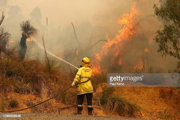 Fire crews control bush fires as they approach properties on Copley Road in Upper Swan on February 02, 2021 in Perth, Australia. The Rapid Damage...