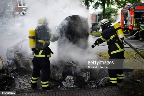 Fire crews extinguish a burning car in the street during the 'Welcome to Hell' antiG20 protest march on July 7 2017 in Hamburg Germany Authorities...