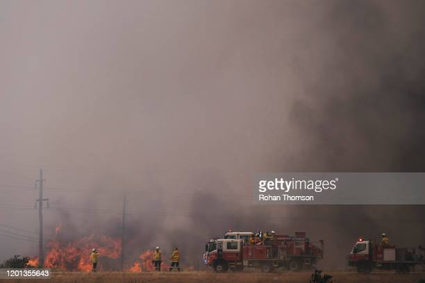 Fire crews work to contain a fire near at the industrial suburb of Beard and residential suburb of Oaks Estate on January 23, 2020 in Canberra,...
