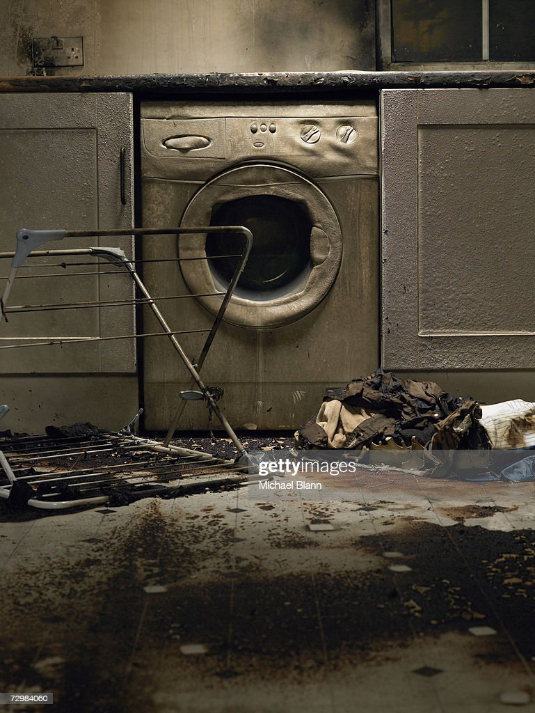 Fire damaged kitchen with washing machine and upturned clothes horse : Stock Photo