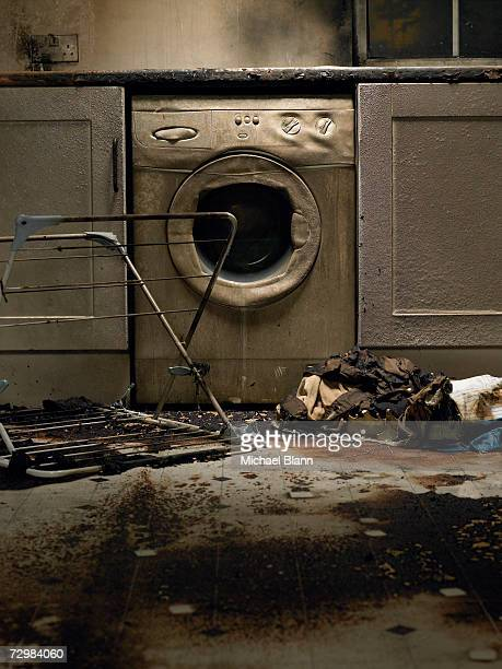 Fire damaged kitchen with washing machine and upturned clothes horse