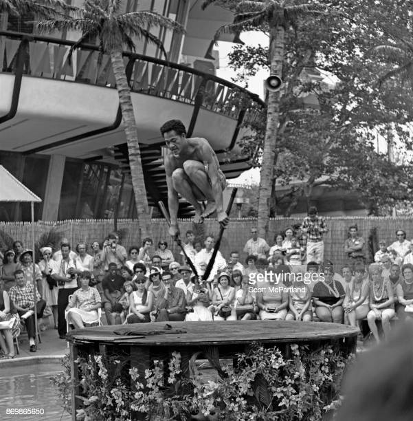 A Fire dancer is captured in mid air as he leaps over his flaming torches for a crowd of spectators at one of the Pavilions during the 196465 World's...