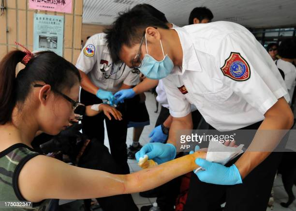 Fire Department ambulance staff help a local resident who was bitten by her own pet cat while getting the rabies vaccine in New Taipei City on July...