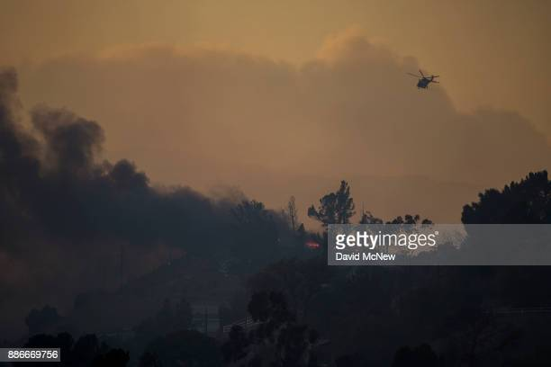 A fire department helicopter flies over burning homes during the Creek Fire on December 5 2017 in Sunland California Strong Santa Ana winds are...