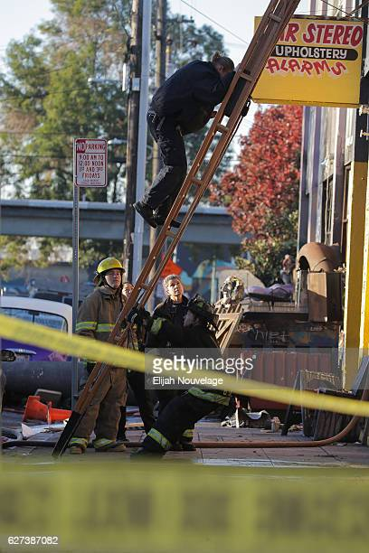 Fire department members investigate the scene of a overnight fire that claimed the lives of at least nine people at a warehouse in the Fruitvale...