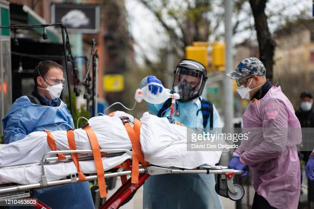 Fire Department of New York medical staff attend to an elderly person experiencing difficulty breathing outside of an apartment building on April 20...