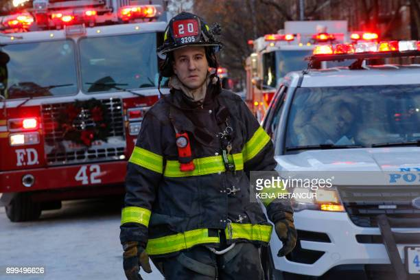 A Fire Department of New York member exits the scene of an apartment fire on December 29 2017 in the Bronx borough of New York City Officials said...
