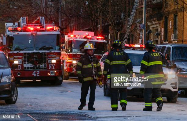 Fire Department of New York personnel work on the scene of an apartment fire on December 29 2017 in the Bronx borough of New York City Officials said...