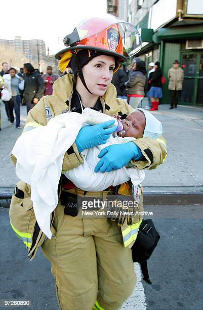 Fire Department paramedic Kyra Arnold carries a baby to an ambulance after the child was removed from a threealarm fire on Lenox Ave in Harlem