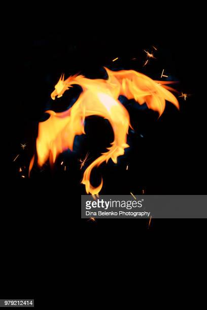 fire dragon made from candle flame on a black background. magical concept with copy space - potion stock photos and pictures