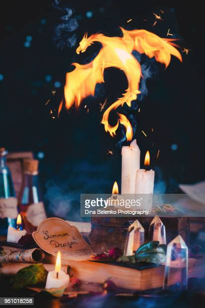 Fire dragon rising from candle flame in a dark fairy tale still life with a witch or wizard workplace, occult crystals, moss, spell scrolls, potions, and herbs. Magical concept with copy space