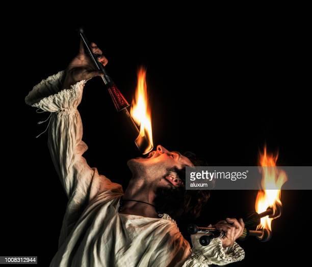 fuego devorador haciendo performance de fuego - faquir fotografías e imágenes de stock