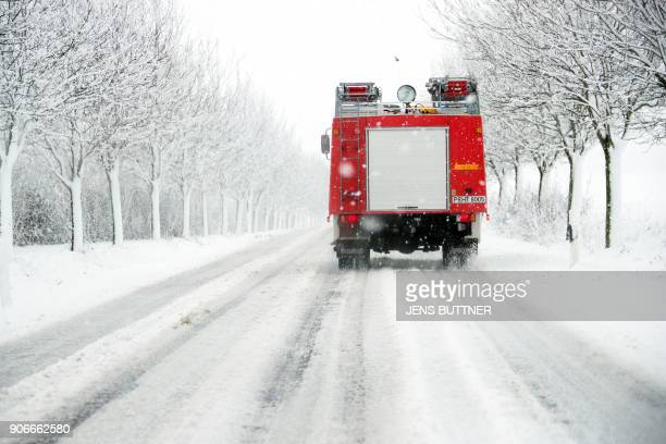 A fire engine drives on a snowcovered road on January 18 2018 near Leezen north eastern Germany as heavy winds and snowfalle are announced Germany...