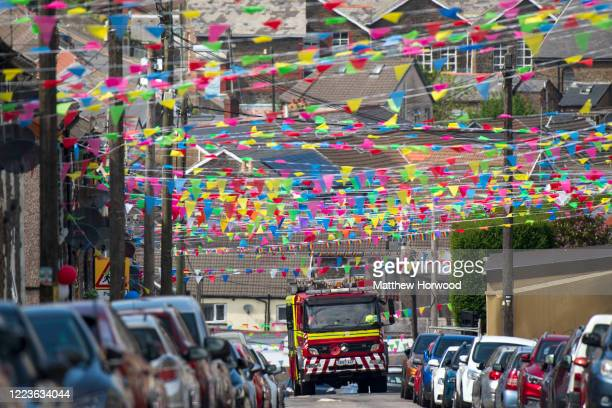 A fire engine navigates a narrow street lined within colourful bunting on May 08 2020 in Penygraig United Kingdom The UK commemorates the 75th...